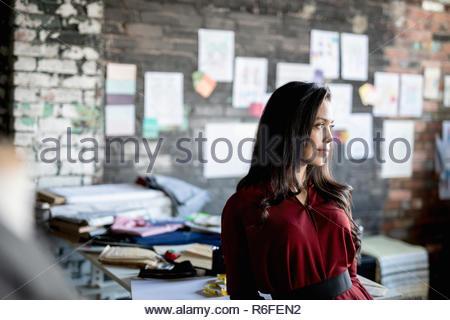 Femmina pensosa designer di moda che guarda lontano in office Foto Stock