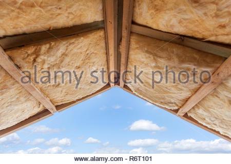Isolamento in fibra di vetro installati nel soffitto inclinato di un nuovo telaio house. Foto Stock