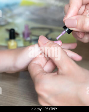 Mom figlia dipinge le unghie delle mani con rosa smalto per unghie sul tavolo Foto Stock