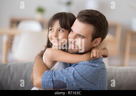 Padre e figlia abbracciando seduti sul divano guardando in telecamera Foto Stock