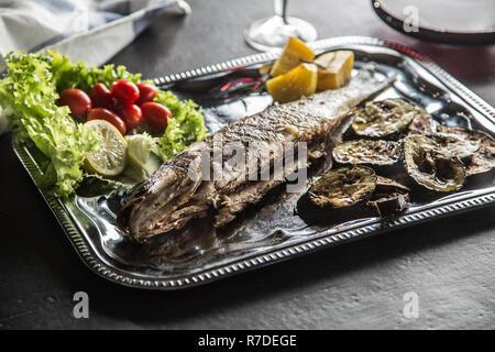 Pesce arrosto sul piatto con carni e verdure alla griglia. Foto Stock