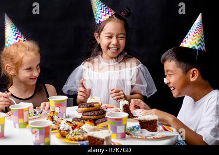 Le ragazze sono liokking al ragazzo divertente con la crema della torta sul suo naso Foto Stock