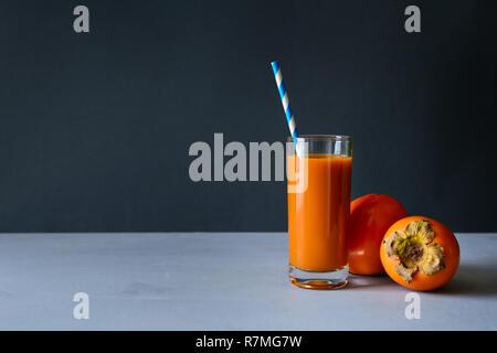 Cachi con succo di cachi in grigio sullo sfondo di legno. Mangiare sano concetto. Copia dello spazio. Foto Stock