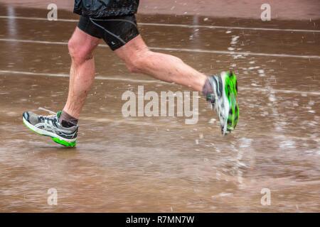 Campo sportivo sotto la pioggia, uomo correre attraverso pozzanghere di acqua, Germania Foto Stock