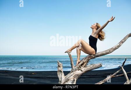 Giovane ragazza felice in costume da bagno seduta sul vecchio albero snag luogo alto le mani in aria, in posa sulla sabbia nera spiaggia del mare. Viaggio il concetto di stile di vita. Foto Stock