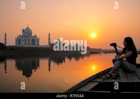 Donna guardando il tramonto Taj Mahal da una barca, Agra, India. Esso fu costruito nel 1632 dall'imperatore Shah Jahan come memoriale per la sua seconda moglie Mumtaz Mah Foto Stock