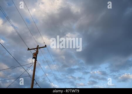 La rete elettrica dell'infrastruttura, polo utilità overhead e linee di alimentazione contro il cielo blu e nuvole nel Wyoming, STATI UNITI D'AMERICA. Foto Stock