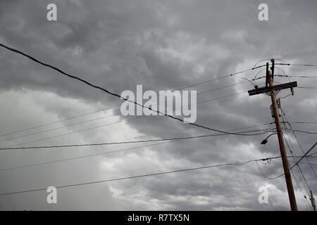 La rete elettrica dell'infrastruttura, polo utilità overhead e linee di alimentazione contro il cielo blu e nuvole nel Wyoming / STATI UNITI D'AMERICA. Foto Stock