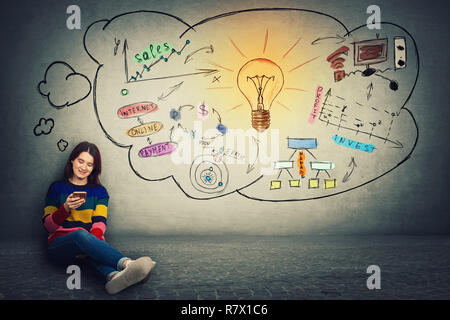 Attraente giovane donna seduta sul pavimento utilizzando il telefono cellulare e il pensiero positivo concetto, le moderne tecnologie di rete e di concetto idea. Lampadina sketc Foto Stock