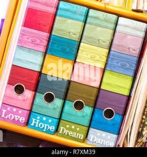 File colorate sul ripiano con didascalie: amore, speranza, sogno, danza. Foto Stock