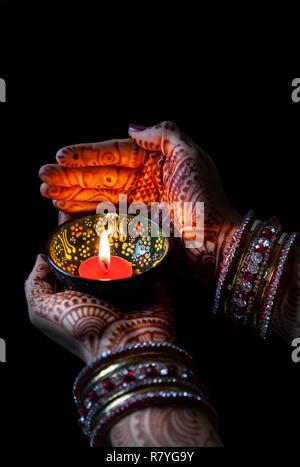 Donna mani con henna tenendo accesa la candela isolata su sfondo nero con tracciato di ritaglio Foto Stock
