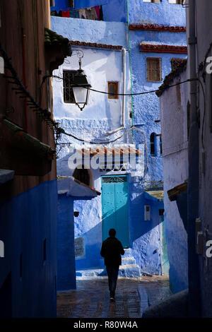 Il Marocco, Chefchaouen, Medina silhouette dell'uomo allo svincolo di wet strette stradine della città vecchia Foto Stock