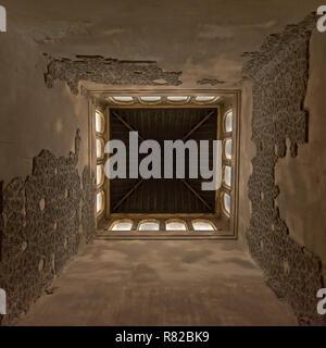 Basso angolo vista centrata all'interno di una torre di, di Nasrid Palace , con gli avanzi decorativi di sculture in pietra e arco di Windows nella parte superiore Alhamb Foto Stock