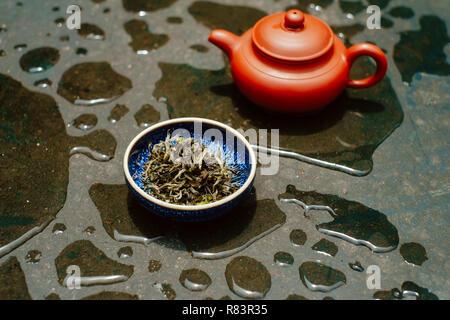 Preparazione del tè in modo cinese (gon fu) con pentola di creta sulla superficie coperta dalle gocce di pioggia Foto Stock