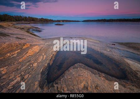Bella sera d'inverno il paesaggio dall'Oslofjord, al forno in Østfold, Norvegia. La parte blu del cielo è l'ombra della Terra. Foto Stock