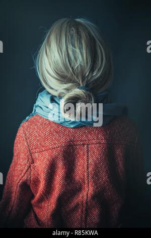 Donna storico in cappotto invernale in possesso di un libro Foto Stock