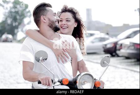 Felice coppia giovane a cavallo di uno scooter in città in una giornata di sole Foto Stock