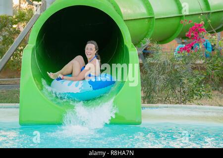 Divertimento al sole-Pretty girl in bikini scende acqua scivolo in piscina. Bella ragazza a cavallo di uno scivolo d'acqua. donna felice di andare verso il basso il ru Foto Stock