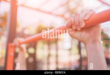 Primo piano della forte atleta facendo pull-up sulla barra orizzontale.Mans fitness con cielo blu in background e aprire lo spazio intorno a lui. Giovane uomo con abiti sportivi nella città. Foto Stock
