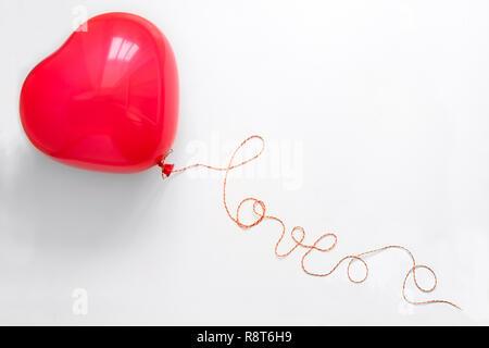Concetto creativo. Mano azienda cuore rosso forma palloncino con amore la parola dal filo bianco su sfondo di legno. Lay piatto. Vista dall'alto. Il giorno di San Valentino celeb Foto Stock