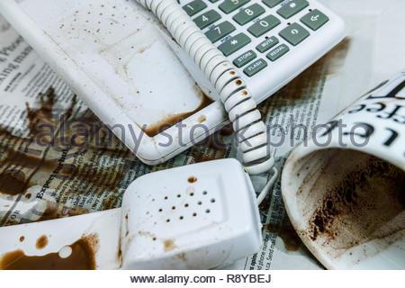 Il caffè versato sul telefono e perni di banco Foto Stock