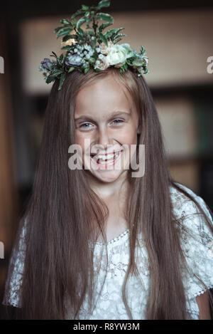 ragazza carina con capelli molto lunghi e una bella corona di fiori sulla testa su uno sfondo sfocato