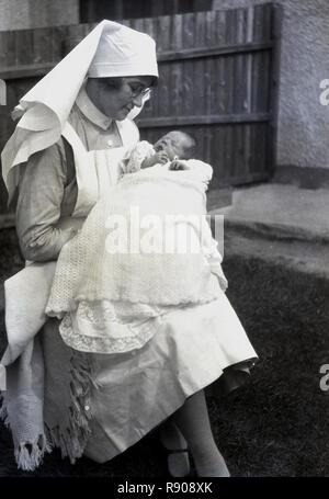 1920s, storico, una levatrice in uniforme al di fuori seduta tenendo un piccolo bambino avvolto in un lenzuolo sul suo giro. In Gran Bretagna in questo momento, home le nascite sono state la norma e alcune ma non tutte le nuove nascite sarebbe accuditi da personale esperto levatrici, coloro che sono stati formalmente addestrato, ostetrica avente stato diventi giuridicamente riconosciuto nel 1902. Dopo WW2 e l'introduzione del NHS nel 1946, le donne hanno avuto accesso ai medici (GPS) nonché delle ostetriche. Foto Stock