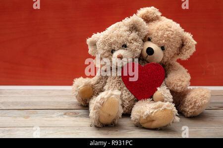 Amore, amicizia concetto, forte abbraccio. Due orsetti di peluche che abbraccia come un giovane su pavimento di legno, Parete Rossa sfondo, copia dello spazio. Foto Stock