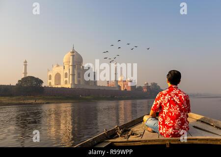 L'uomo a guardare il tramonto Taj Mahal da una imbarcazione in legno con uccello sorvolano. Foto Stock
