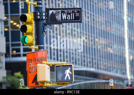 Wall street sign in primo piano e un enorme edificio sfocata in background in Manhattan. Foto Stock