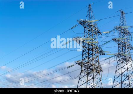 Due supporti di trasmissione ad alta tensione con linea di fili di potenza elettrica sul cielo blu sullo sfondo. Foto Stock