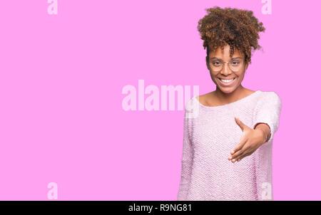 Bella giovane americano africano donna che indossa gli occhiali su sfondo isolato sorridente cordiale offrendo stretta di mano come saluto e accogliente. Successo