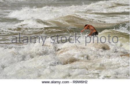 Un barbuto Caucasian maschio con un lupo-tatuaggio sul suo tronco, battaglie per rimanere in piedi sulla sua tavola da surf, in acque bianche schiumose; navigazione a Yamba, NSW. Foto Stock