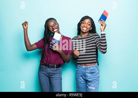 Due donne africane con volo biglietti pronti per i viaggi isolati pastello su sfondo blu Foto Stock