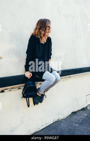 Giovane donna ondulata con capelli biondi seduto sulla ringhiera cercando da parte. Schietto stile di vita foto di moda donna in posa sulla strada della citta'. Foto Stock