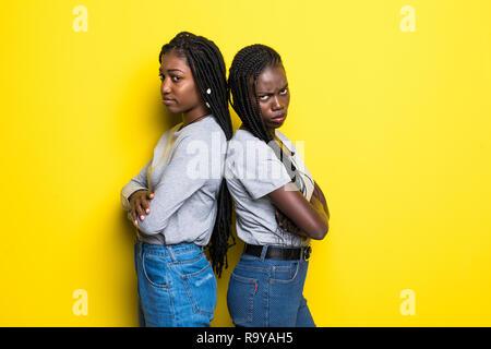 Portriat di due donne africane in piedi con le braccia incrociate dopo litigare isolate su sfondo giallo Foto Stock