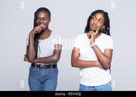 Portriat di due negative delle donne africane in piedi con le braccia incrociate dopo litigare su sfondo bianco Foto Stock