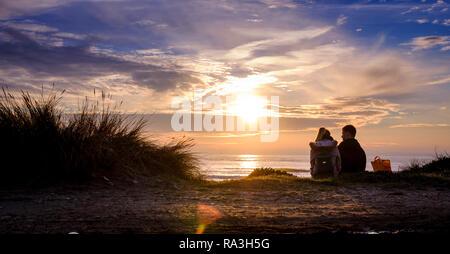 Un giovane seduto sul bordo di dune di sabbia sulla West Wittering spiaggia nelle vicinanze del Chichester, West Sussex. Foto Stock