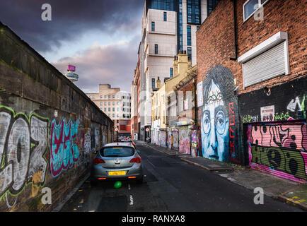 Un moody scena del vicolo della troncatrice Street, Liverpool con un John Lennon murale e altri graffiti. Foto Stock