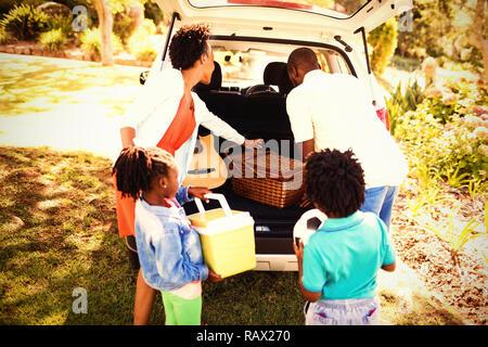 La famiglia felice di prendere gli oggetti fuori della vettura Foto Stock