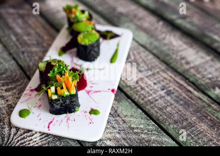 Materie vegano rotoli di sushi con verdure e salsa verde con lo styling di cibo nel ristorante Foto Stock
