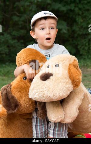 Bambino con grande giocattolo di peluche cani esprimendo sorpresa gioiosa in un parco Foto Stock