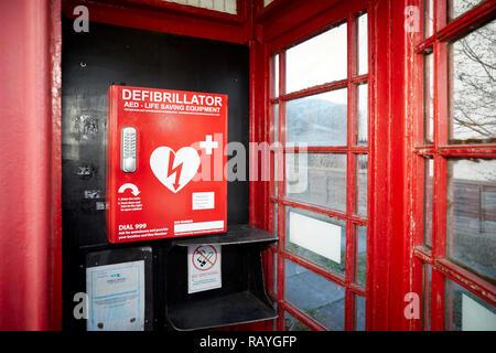 La defibrillazione di emergenza il defibrillatore semiautomatico esterno (AED) situato in un vecchio telefono rosso scatola in un villaggio di Lancashire Foto Stock