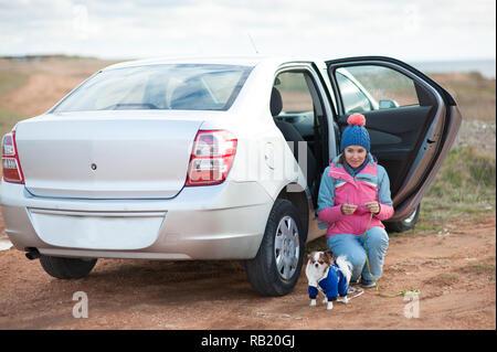 Giovane donna caucasica in inverno tuta vicino auto con piccolo cane domestico Foto Stock