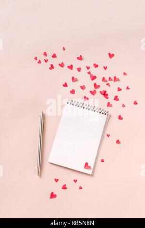 Notebook e cuori rossi isolato su sfondo beige, copia dello spazio. Minima laici piatta con la pianificazione per il giorno di San Valentino, amore e romanticismo concetto, vista dall'alto Foto Stock