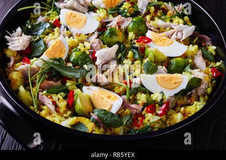 Close-up di deliziose Kedgeree con scaglie di pesce affumicato, uova sode, riso, kale, i cavoletti di Bruxelles, le spezie e le erbe in un forno olandese su un nero woo Foto Stock