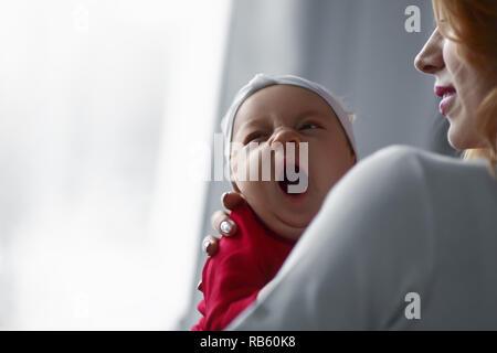 Amorevole Madre Cuddling Sleeping Neonato figlia sulla spalla. Foto Stock