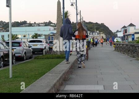 Giovane ragazzo e una ragazza camminare per la strada Teignmouth DEVON REGNO UNITO Foto Stock