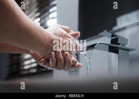 L'uomo bianco di formazione di schiuma e si lava le mani con sapone in bagno mantenendo l'acqua del rubinetto in esecuzione. Concetto per l'igiene del corpo, la prevenzione delle malattie, igiene personale, e la conservazione di acqua Foto Stock