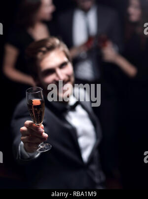 Elegante giovane alzando il vetro in un toast Foto Stock